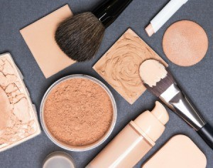 Various face powders and foundations with brushes displayed on grey surface