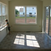 Child Looking out Window in a room with vinyl flooring