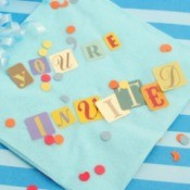 """""""You're Invited"""" Spelled out on a napkin"""