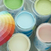 Gallon paint cans with several different colors and had holding paint color sample strips