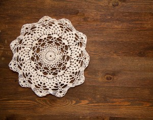 crochet lace doily on dark wood background