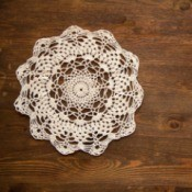 crochet lace doily on dark wood background
