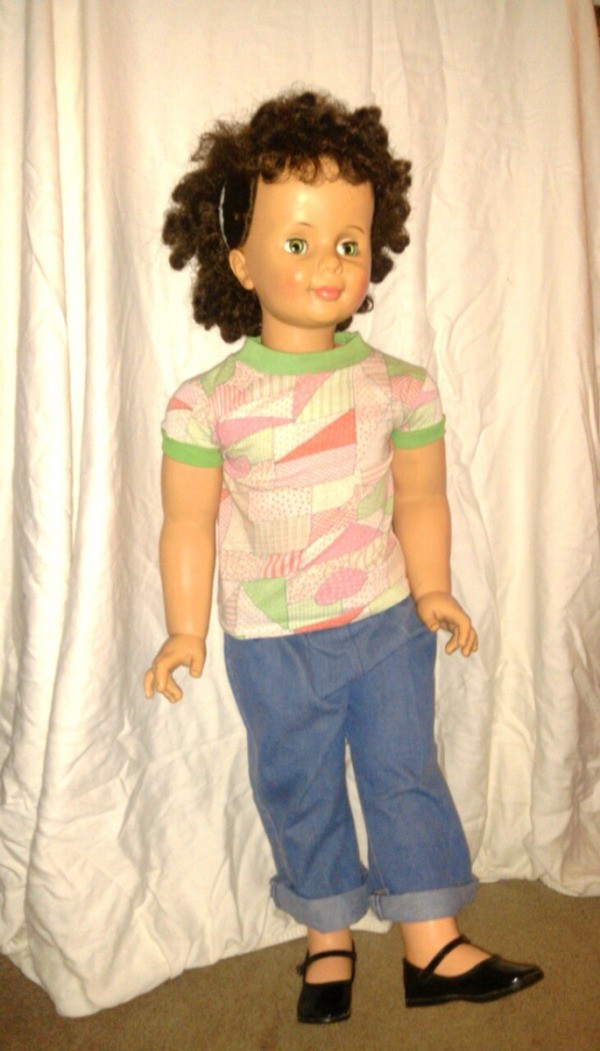 A cleaned up brown haired doll dressed in blue jeans.