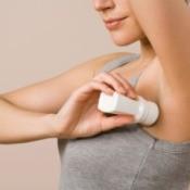 Woman in tank top applying deodorant