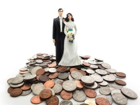 Bride and groom figures standing on a smile of coins