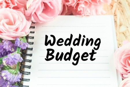 Notebook labelled Wedding Budget surrounded by flowers