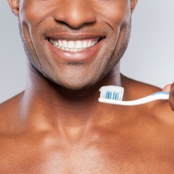 Close up of a man with a bright white smile holding a toothbrush