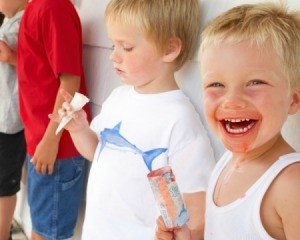 Smiling little boy with red ice pop and red coloring all around his mouth, dripping down his next and onto his white shirt
