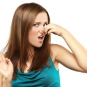 Woman with disgusted expression holding her nose and holding her other hand up in front of her