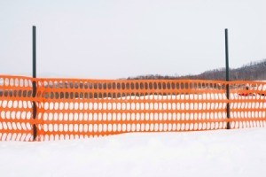 Bright Orange plastic mesh snow fence in a field of snow