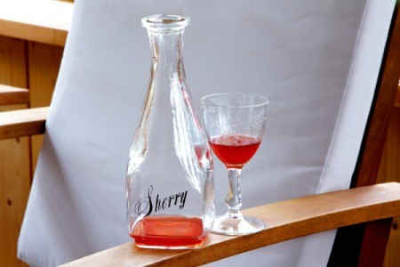 Bottle labelled Sherry next to a class containing sherry