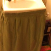 A sink skirt attached with tape.