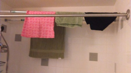 laundry drying on curtain tension rods