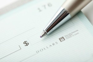 Close up of pen laying on dollar amount portion of check