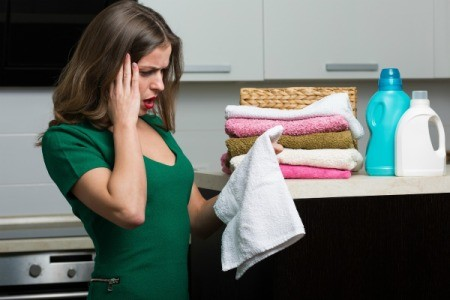 Distressed woman looking at white towel in laundry room
