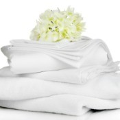 Stack of white linens with a white flower resting on top