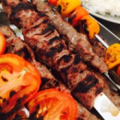 A skewer of Persian Lamb Kabobs with roasted vegetables.