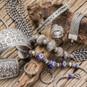 A pile of silver jewelry on a wooden surface.