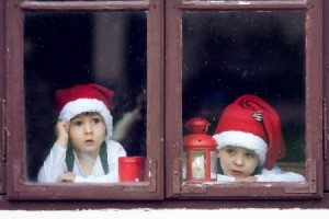 Two boys in santa hats looking out window in hopes of seeing Santa