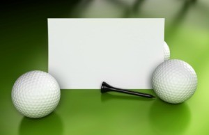 Blank card golf balls and golf tees displayed against a green background