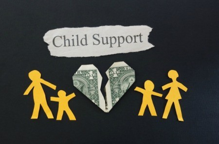 Paper art of stick figure man and woman with stick figure children separated by a torn dollar bill in the shape of a heart