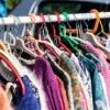 rack of women's sweaters at a flea market