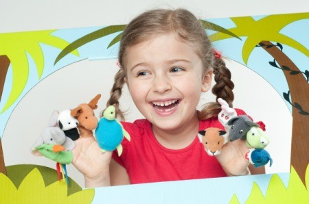 Little girl with finger puppets in puppet theater