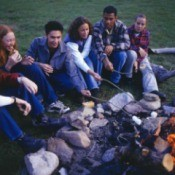 Teens roasting marshmallows around a campfire.