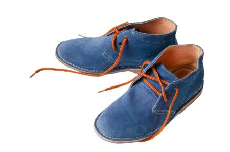 Pair of blue suede shoes on white background