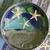 display of beach sand, sea glass, and tiny sea stars