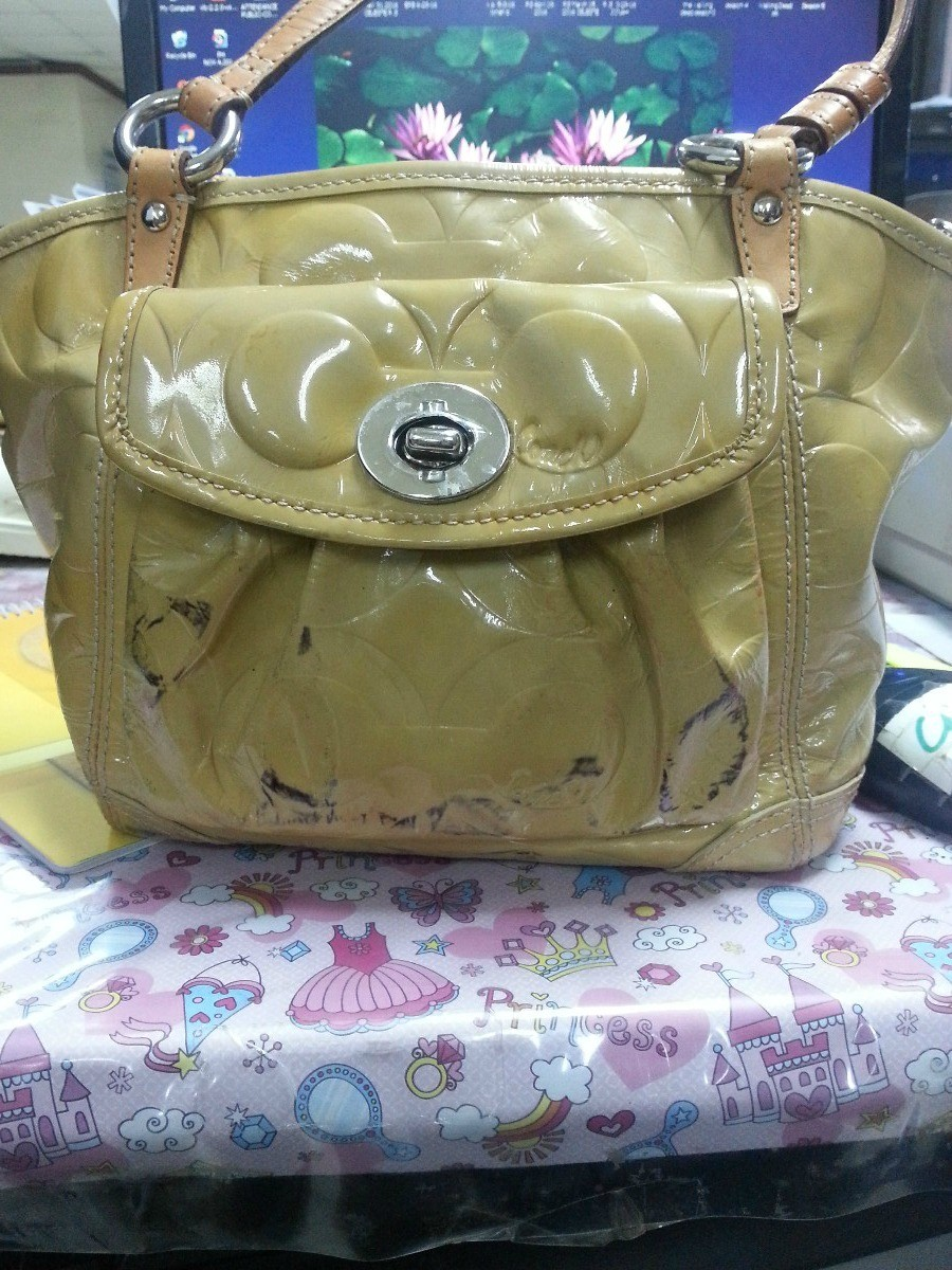 0af565b92429 I have a yellow Coach patent leather tote bag. Can someone please help me  with how to remove the black stains  Thank you.
