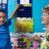 Teacher with child learning about money
