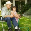 Grandfather sitting in chair and helping Granddaughter water the lawn