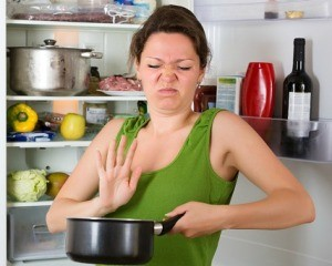Woman with disgusted face by refrigerator