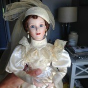 doll wearing fancy off white dress with matching hat