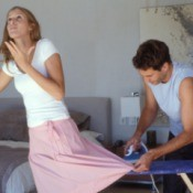 Man ironing women's skirt as she is trying to walk away