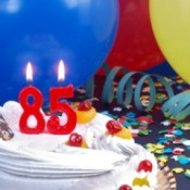 Cake with candles that say 85 surrounded by balloons, ribbons, and confetti