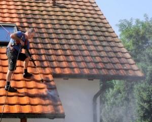 Man power washing tile roof