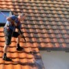 Man power washing tile roof