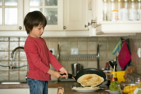 Young boy making crepes on the stove