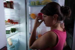 Woman standing in front of open refrigerator door holding her nose
