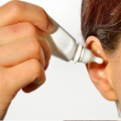Adult using a dropper to insert liquid into ear
