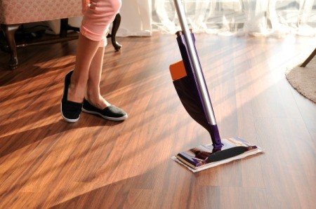 Woman's legs and Swiffer WetJet style electronic mop on wooden floor