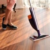 Woman's legs and Swiffer WetJet style electronic mop on wooden floor