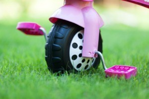 Close up of the front wheel of a pink toddler trike