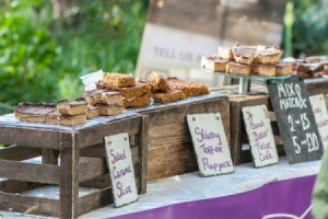 Plates of baked goods on crates with cards in front listing names and prices