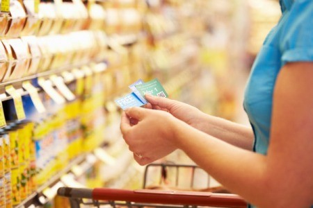 Woman Looking at Coupons in Supermarket