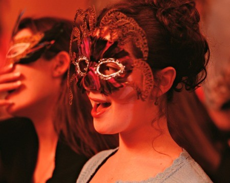 Two young girls in masquerade masks at a party