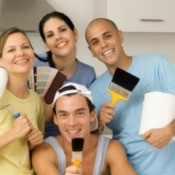 Group of people holding painting supplies and samples in a white kitchen