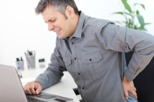 Man at computer grasping his back in pain